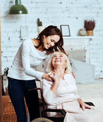 senior woman on a wheelchair smiling with her caregiver