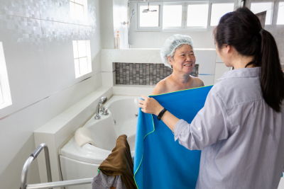 female caregiver assisting senior woman taking a shower in bathroom